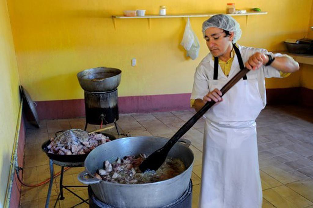 COSTA RICA, MAN DEEP FRYING CHICHARRONES, DEEP FRIED PORK : Stock Photo