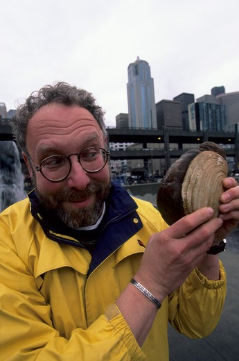 USA, WASHINGTON, SEATTLE, DAVID GORDON WITH GEODUCK, SEATTLE SKYLINE IN BACKGROUND : Stock Photo