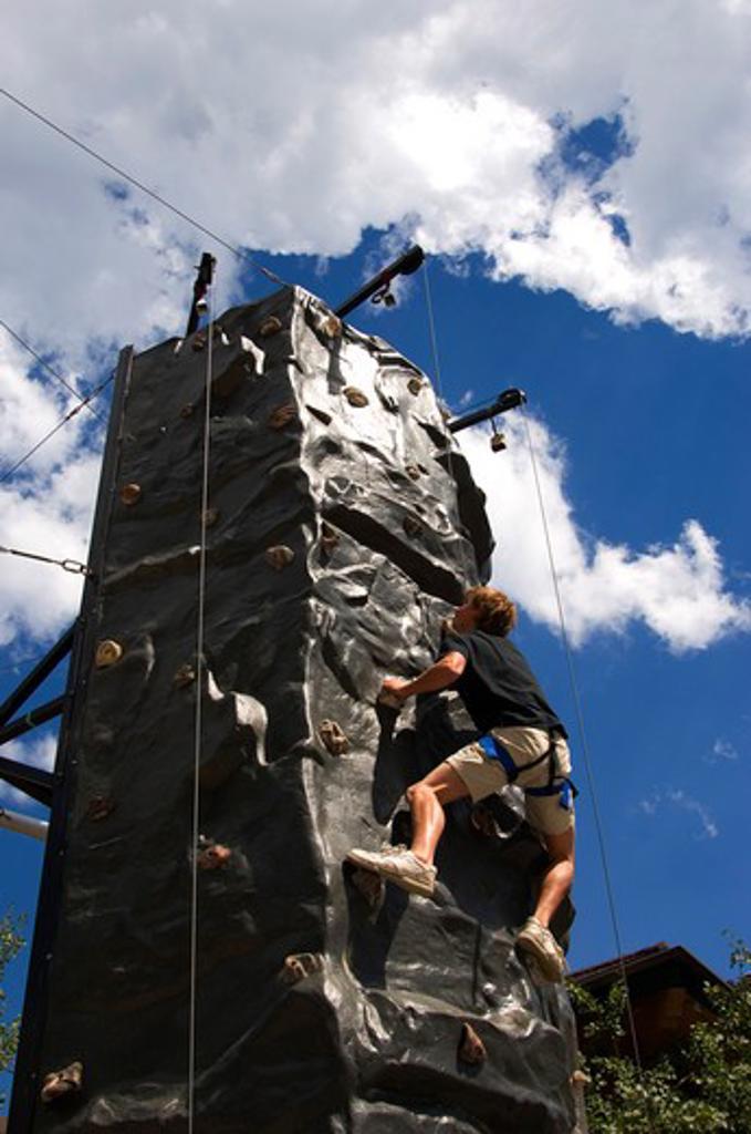 USA, IDAHO, NEAR SANDPOINT, SCHWEITZER MOUNTAIN RESORT, TEENAGER ON CLIMBING WALL : Stock Photo
