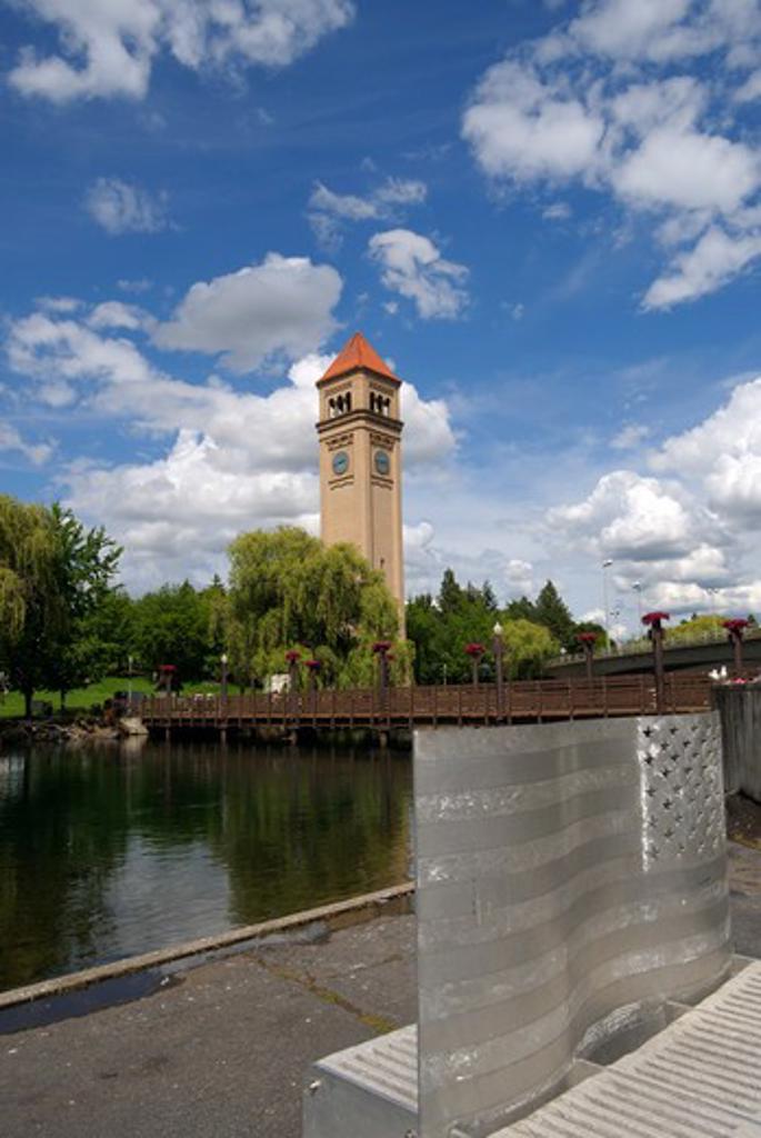 USA, WASHINGTON STATE, SPOKANE, RIVERFRONT PARK, ALUMINUM BENCH (AMERICAN FLAG) ART, CLOCK TOWER IN BACKGROUND : Stock Photo