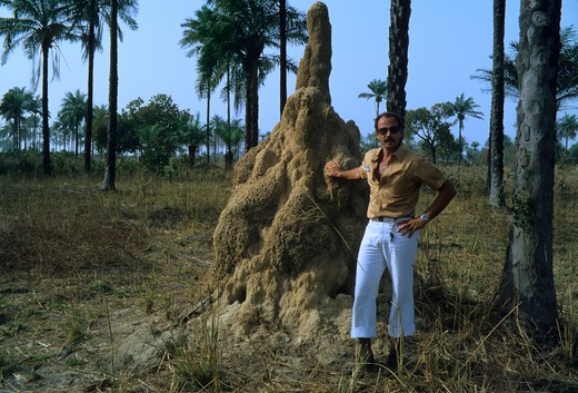 GAMBIA, GAMBIA RIVER, MAN STANDING NEXT TO TERMITE MOUND : Stock Photo