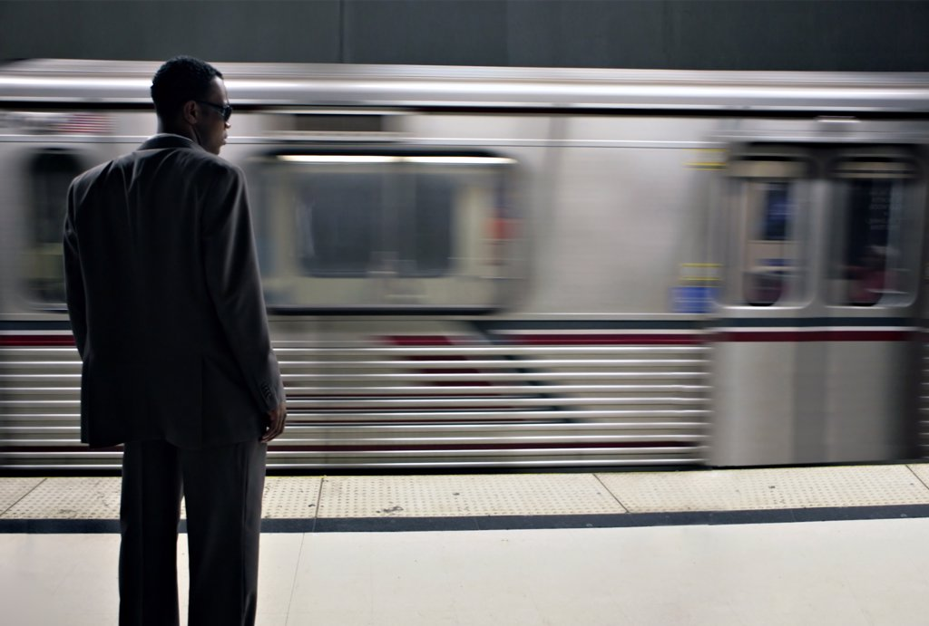 Stock Photo: 4165R-1160 African American Businessman Waiting for the Subway Train. Intentional Blur, Image is Shot in High ISO