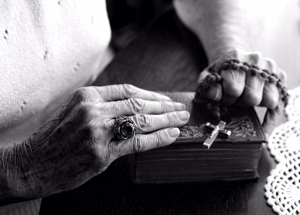 Elderly Woman's Hands Holding Her Bible and Rosary : Stock Photo