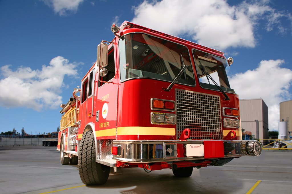 Stock Photo: 4165R-1776 Fire engine on pavement with clouds in the background