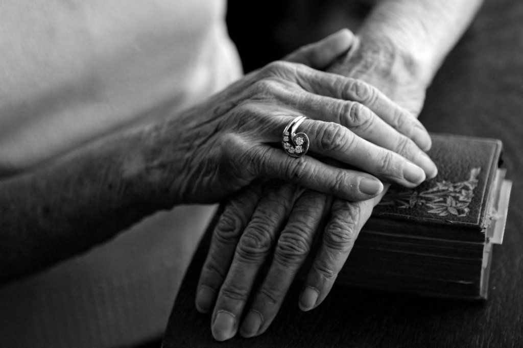 Old Woman's Hands on Her Bible Wearing Her Vintage Ring : Stock Photo