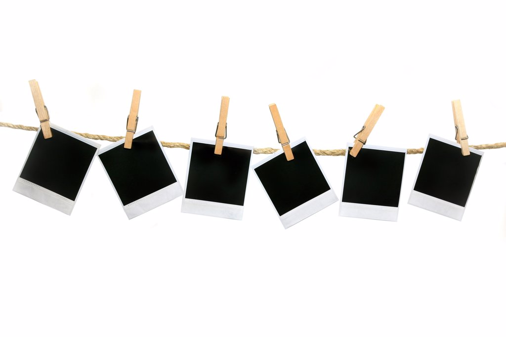 Stock Photo: 4165R-2293 Crooked Old Polaroid Film Blanks Hanging on a Rope Held By Clothespins With No Drop Shadow