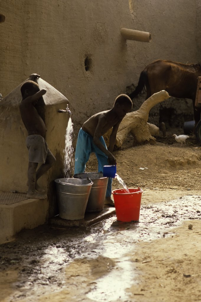 Mali, Djenne, Street Scene Boys Getting Water From Well : Stock Photo