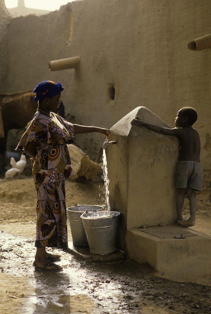 Stock Photo: 4168-10583 Mali, Djenne, Street Scene Girl Getting Water From Well