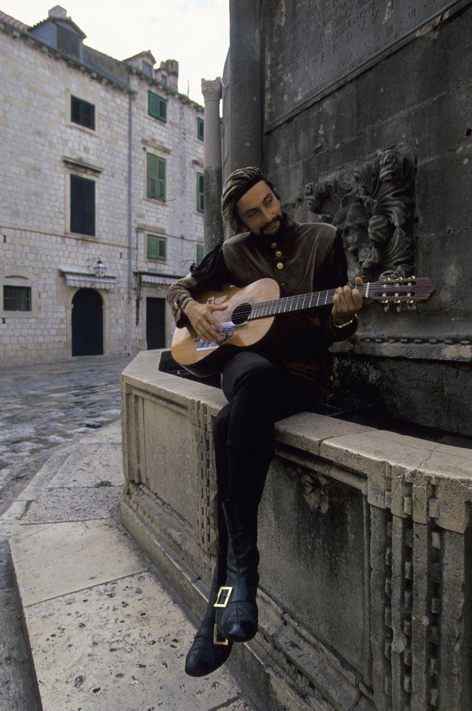 Stock Photo: 4168-9928 Croatia, Dubrovnik, Street Musician In Renaissance Clothing Playing Guitar