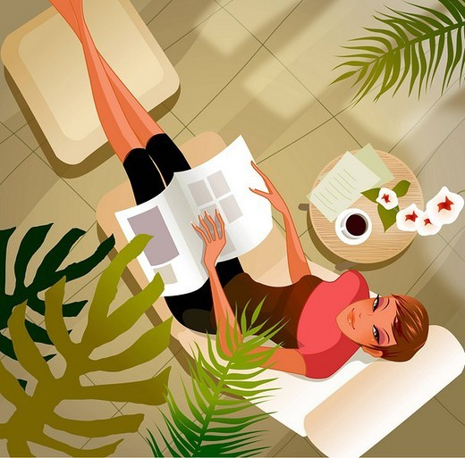 High angle view of a woman with a magazine lying on a lounge chair : Stock Photo