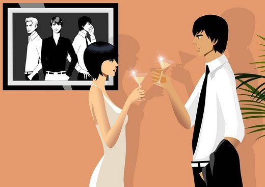 Side profile of a couple toasting with martini glasses : Stock Photo