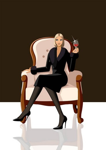 Woman sitting in an armchair and holding a glass of red wine : Stock Photo