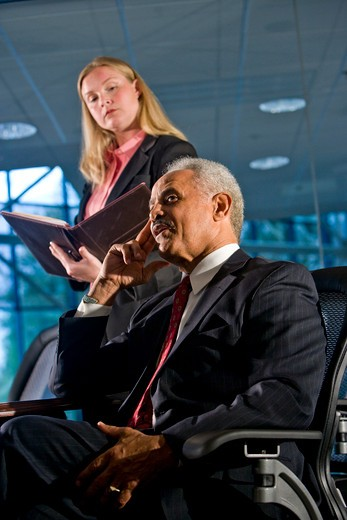 Businessman and female assistant in a boardroom meeting : Stock Photo