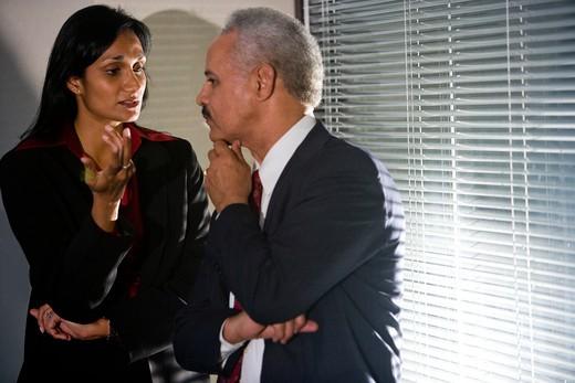 Multi-ethnic businesspeople having discreet conversation in corner of meeting room : Stock Photo