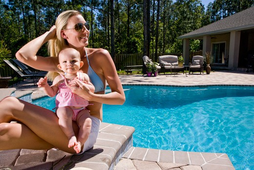 Stock Photo: 4172R-1021 Mother and baby playing by swimming pool