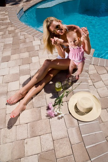 Mother and baby playing by swimming pool : Stock Photo