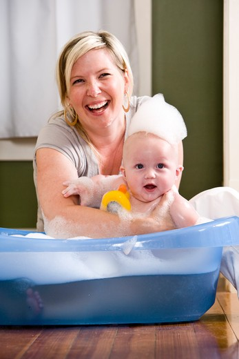 Happy mother bathing cute baby : Stock Photo