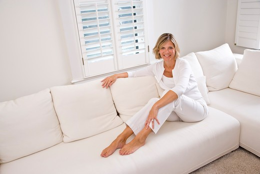 Stock Photo: 4172R-1138 Woman relaxing at home in white living room