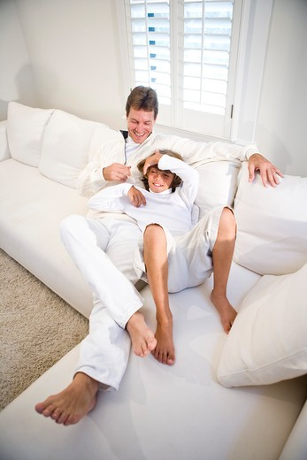 Stock Photo: 4172R-1173 father and son relaxing on white sofa