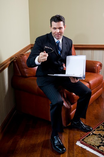 Stock Photo: 4172R-1256 Businessman on couch looking up holding notebook