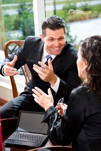 Businessman talking with female Hispanic coworker : Stock Photo