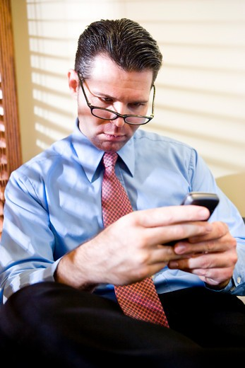 Serious businessman texting on mobile phone : Stock Photo