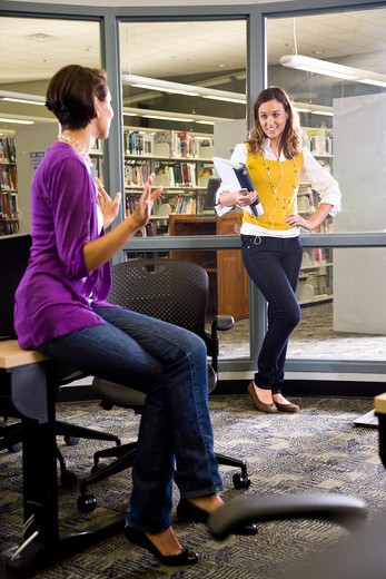 Stock Photo: 4172R-1356 Two female university students talking in library