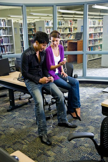 Two college students with music players in library : Stock Photo