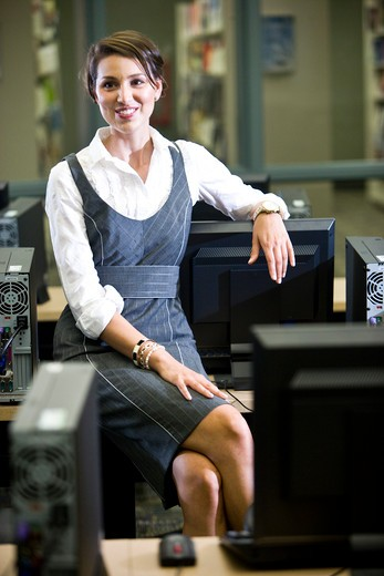 Young woman sitting in library computer room : Stock Photo