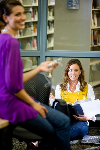 Two female university students talking in library : Stock Photo