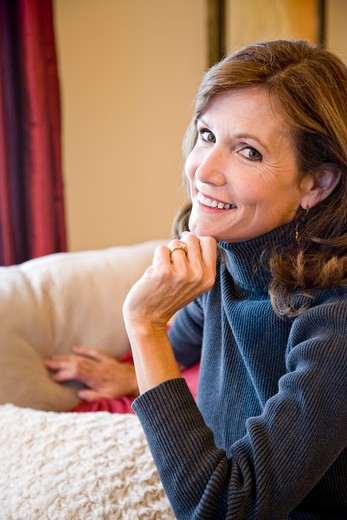 Close up of mature woman sitting on sofa : Stock Photo