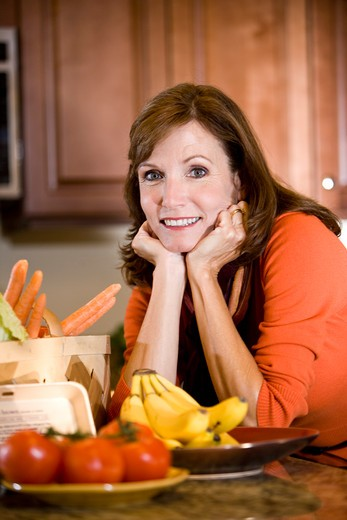 Mature woman in kitchen with fresh ingredients : Stock Photo