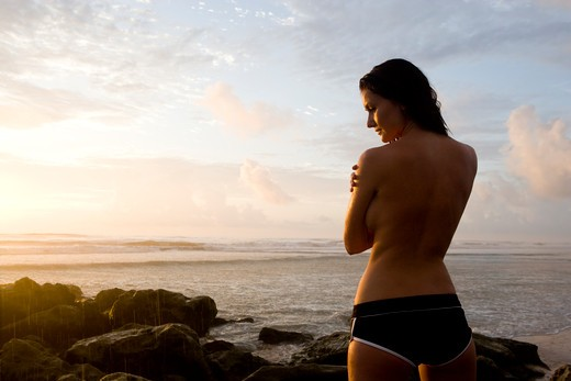 Silhouette of woman in swimsuit watching sunrise : Stock Photo
