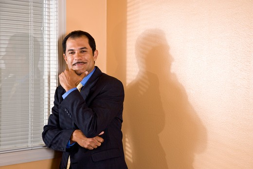 Confident middle-aged Hispanic businessman by office window : Stock Photo