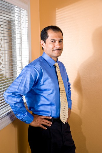 Stock Photo: 4172R-1497 Confident middle-aged Hispanic businessman with hands on hips