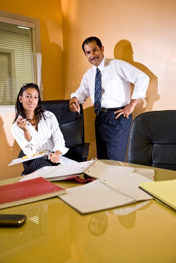 Stock Photo: 4172R-1519 Middle-aged Hispanic businessman and young assistant in office boardroom