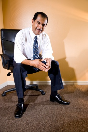 Stock Photo: 4172R-1523 Confident middle-aged Hispanic businessman sitting on office chair