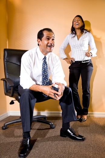 Confident middle-aged Hispanic businessman sitting on office chair by young assistant : Stock Photo