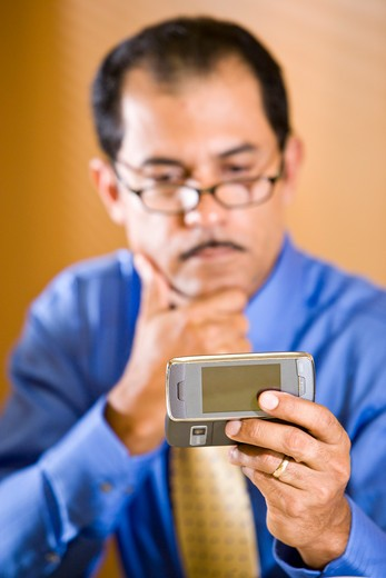 Stock Photo: 4172R-1543 Middle-aged Hispanic businessman reading text message on mobile phone