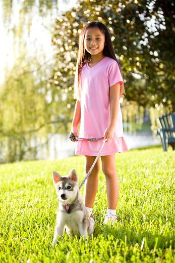 Young Asian girl walking puppy on leash on grass : Stock Photo