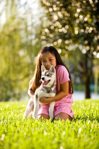 Young Asian girl hugging puppy sitting on grass : Stock Photo