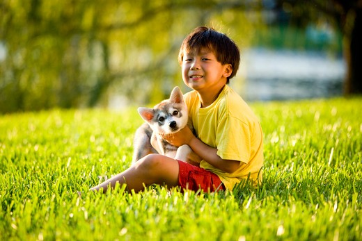 Stock Photo: 4172R-1571 Young Asian boy hugging puppy sitting on grass