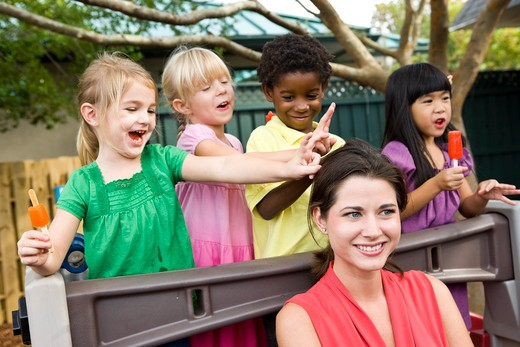 Young preschool children playing in daycare with teacher : Stock Photo