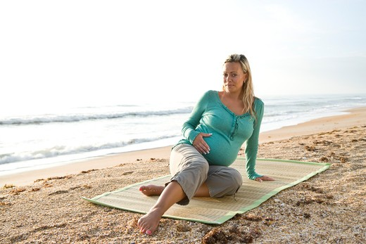 Young pregnant woman sitting on mat at beach : Stock Photo
