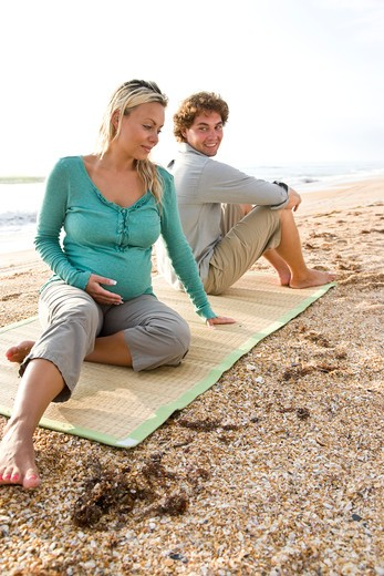 Young pregnant couple sitting on mat at beach : Stock Photo