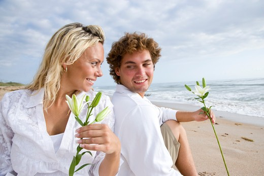 Stock Photo: 4172R-1614 Happy young couple sitting together on beach