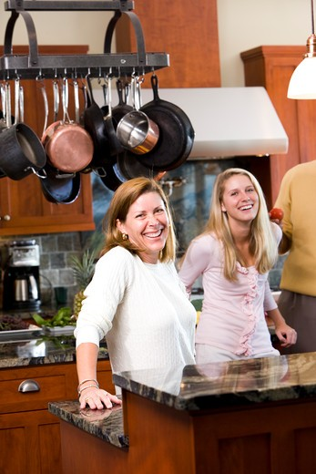 Mother standing in kitchen with teenage daughter : Stock Photo