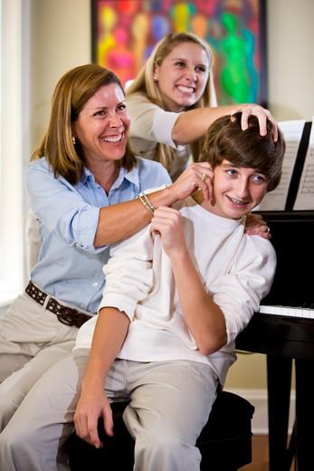 Stock Photo: 4172R-1720 Family having fun teasing teenage boy at home