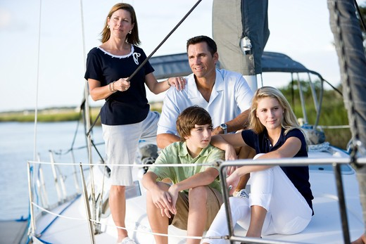 Family with teenagers relaxing together on boat : Stock Photo