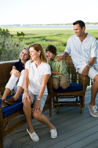 Family of four sitting together outdoors on terrace : Stock Photo